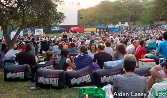 Audience on bean bags and picnic blankets waiting for the open air cinema to start