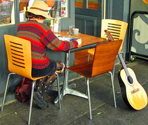 Woman with guitar and book at an outside cafe table