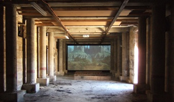 A Sydney Biennale film running in a hall with pillars on Cockatoo island