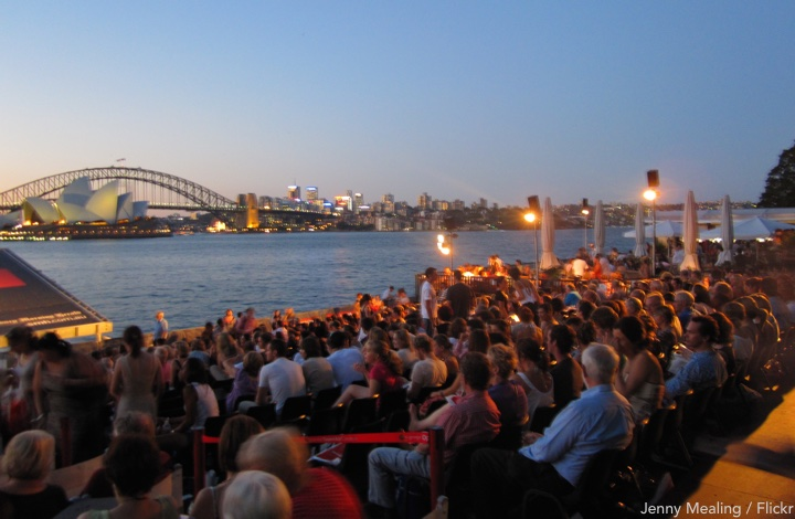 Open air cinema: patrons seated at the harbour's edge at sunset, Sydney opera house and harbour bridge in their view.