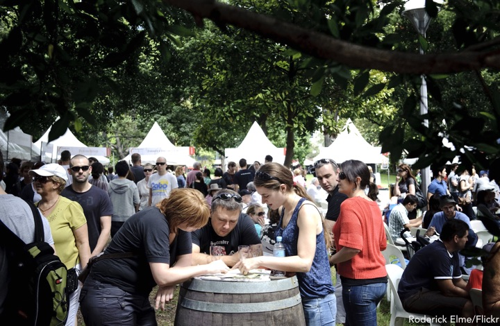 People comparing notes around a wine barrel at the NSW Food and Wine Festival Sydney in Hyde Park
