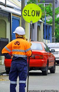 Girl with stop sign directing traffic: working holiday visa Australia