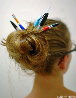 Woman with pens in her hair: working holiday visa Australia
